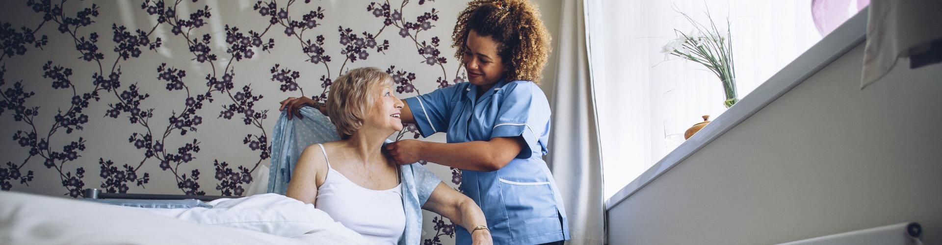 Nurse helping a senior woman get dressed